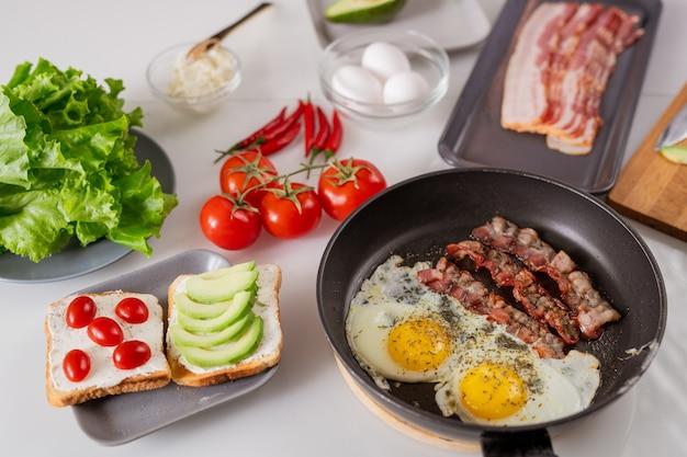 Twee smakelijke vegetarische sandwiches, koekenpan met gebakken eieren en spek, rijpe verse tomaten, sla en hete chili pepers op tafel