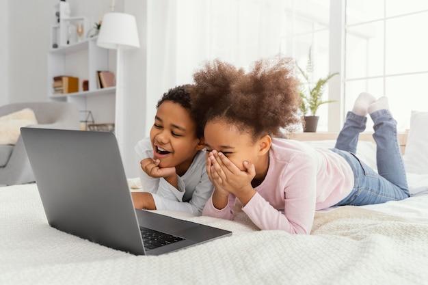 Twee smileys en zussen die thuis samen op laptop spelen
