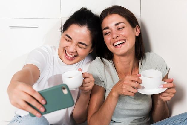 Twee smileyvrouwen die thuis in de keuken een selfie nemen