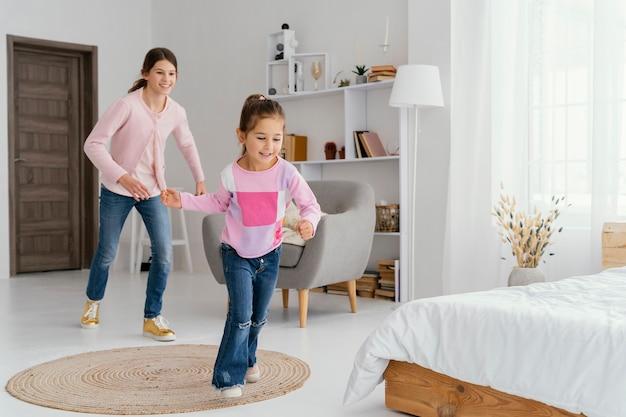 Twee smileyzusters die thuis spelen Premium Foto