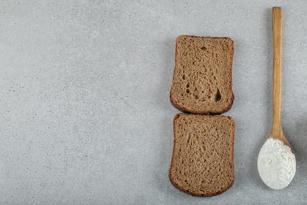 Twee sneetjes bruin brood met houten lepel bloem.