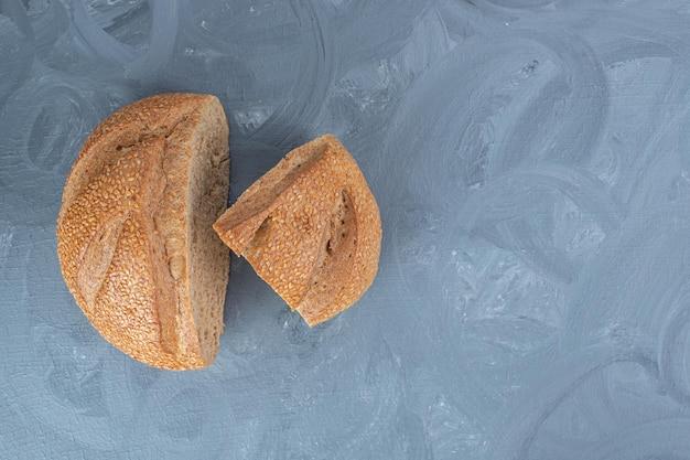 Twee sneetjes roggebrood weergegeven op marmeren tafel.