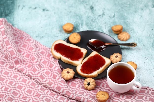 Twee sneetjes toast met rode jam in zwarte plaat met koekjes rond en een witte kop thee op een blauwe stenen tafel.