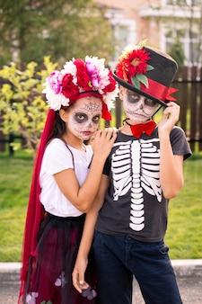 Twee sombere halloween-kinderen met geschilderde gezichten die dicht bij elkaar tegen een landhuis staan en je buiten aankijken