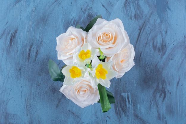 Twee soorten bloemen geplaatst in roze emmer op blauw.