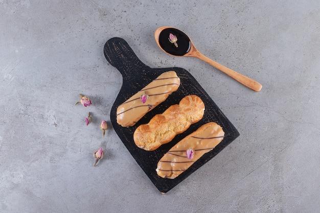 Twee soorten chocolade-eclairs met een lepel chocolade op stenen tafel.