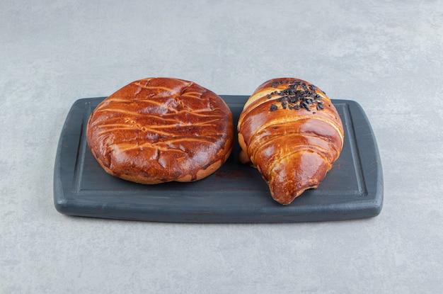 Twee soorten gebak op zwart bord.