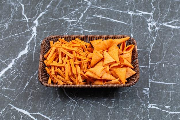 Twee soorten knapperige chips in houten mand.