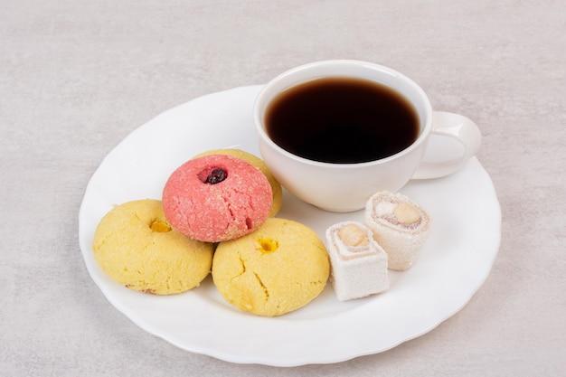Twee soorten koekjes, lekkernijen en kopje thee op witte plaat.