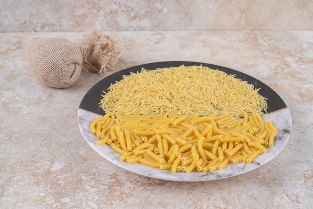 Twee soorten ongekookte macaroni op een mooi bord