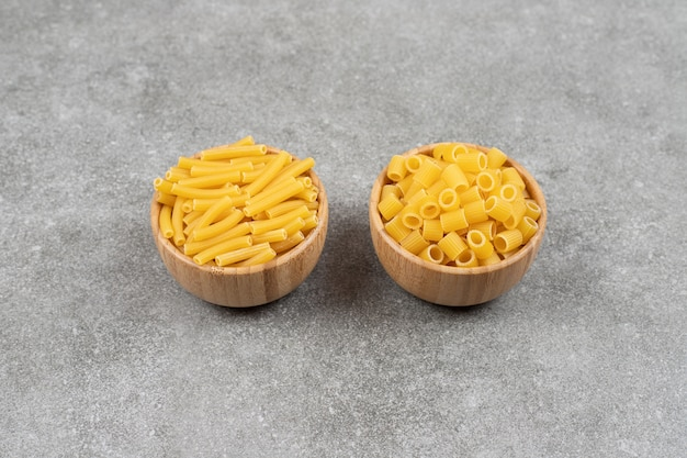 Twee soorten ongekookte macaroni op marmeren oppervlak