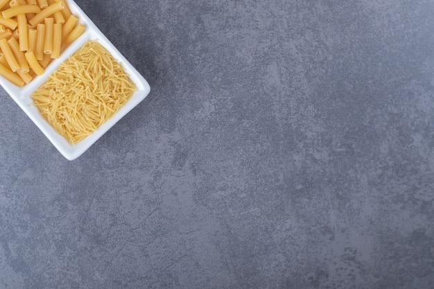 Twee soorten ongekookte pasta op witte plaat.