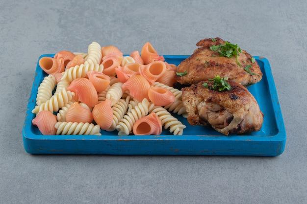 Twee soorten pasta en gegrilde kip op blauw bord.