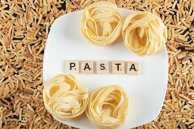 Twee soorten pasta op een witte plaat en verspreid over het oppervlak.