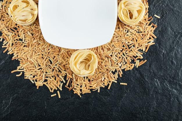 Twee soorten pasta verspreid over een witte plaat.