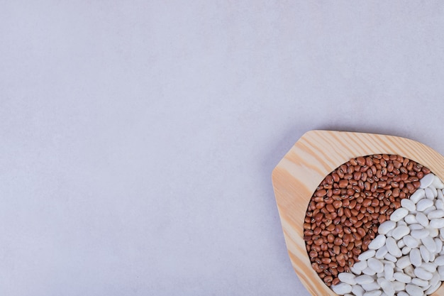 Twee soorten rauwe bonen en erwten in houten plaat.