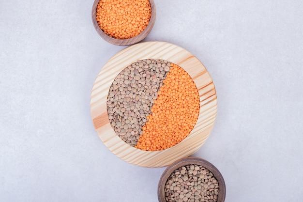Twee soorten rauwe bonen en linzen in houten plaat en kommen.