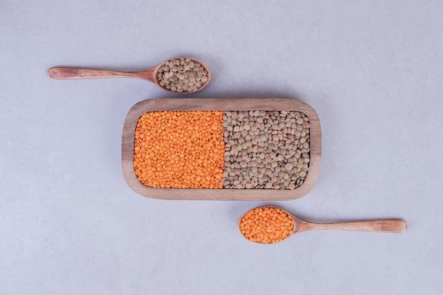 Twee soorten rauwe bonen en linzen in houten plaat met lepels.
