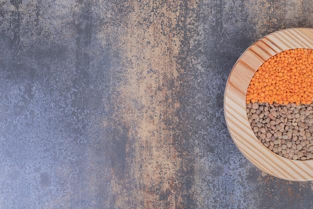 Twee soorten rauwe bonen en linzen in houten plaat.