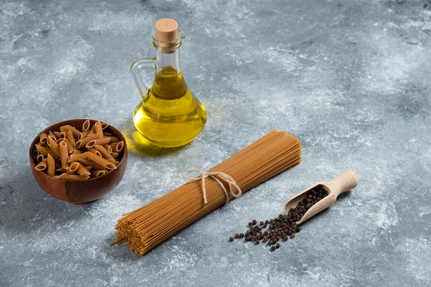 Twee soorten rauwe pasta en een glazen fles olie.