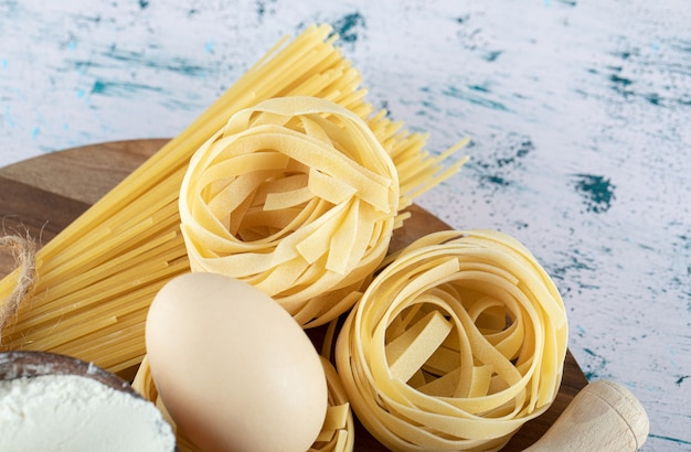 Twee soorten rauwe pasta met ei en kom bloem op een houten bord.