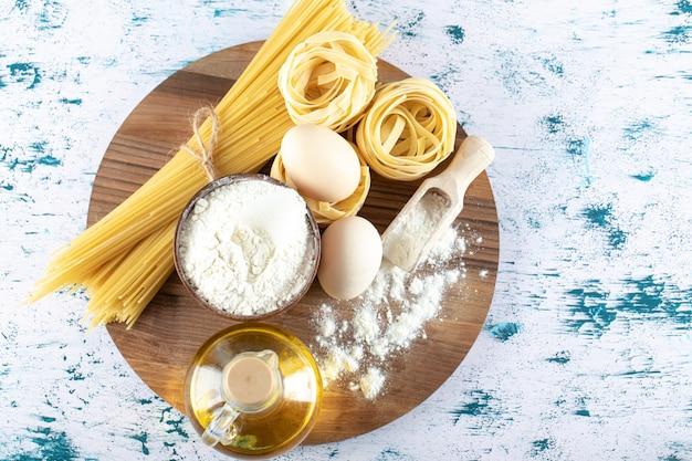Twee soorten rauwe pasta met olie, ei en kom bloem op een houten bord.