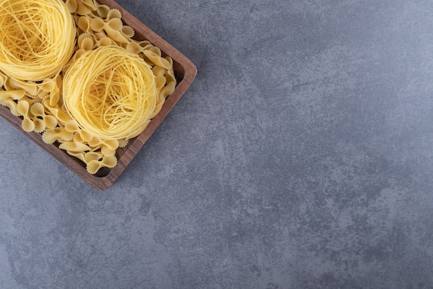 Twee soorten rauwe pasta op een houten bord.