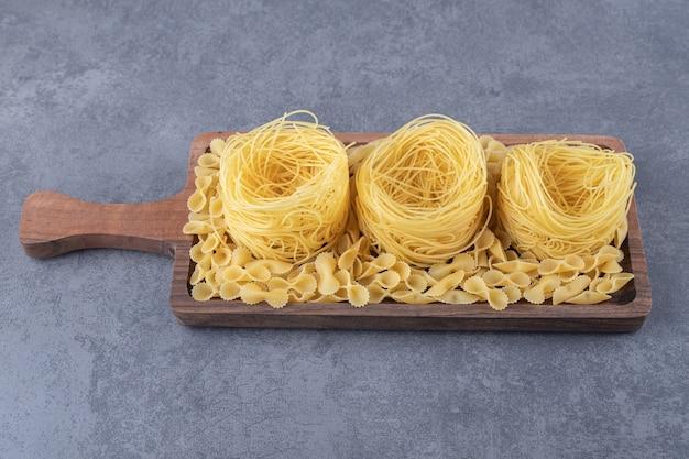 Twee soorten rauwe pasta op een houten bord. Gratis Foto