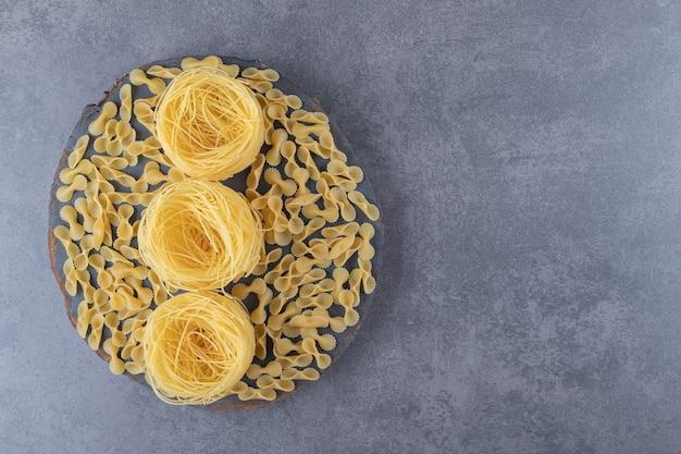 Twee soorten rauwe pasta op een stuk hout.