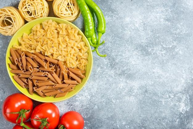 Twee soorten rauwe pasta op groene plaat met rauwe pasta nesten.