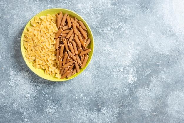 Twee soorten rauwe pasta op groene plaat.
