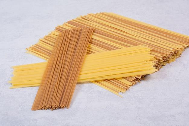 Twee soorten ruwe spaghettideegwaren op witte oppervlakte
