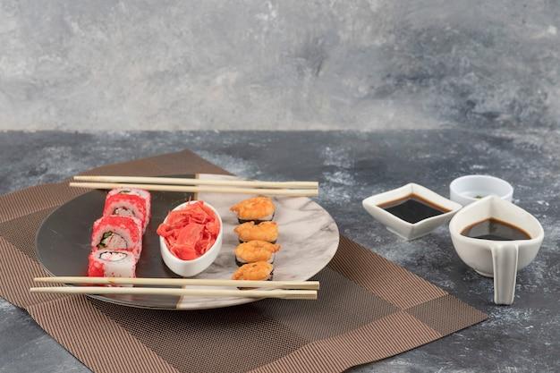 Twee soorten smakelijke sushibroodjes op marmeren plaat met sojasaus