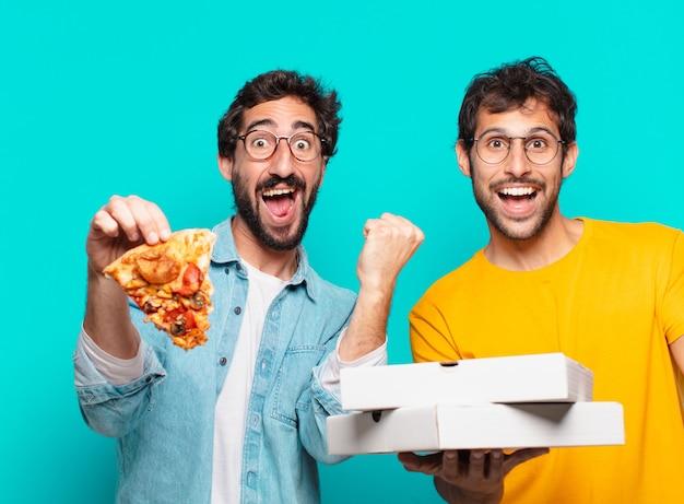 Twee spaanse vrienden die een succesvolle overwinning vieren en afhaalpizza's houden