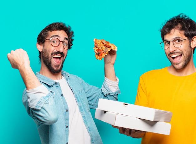 Twee spaanse vrienden die een succesvolle overwinning vieren en pizza's houden om mee te nemen