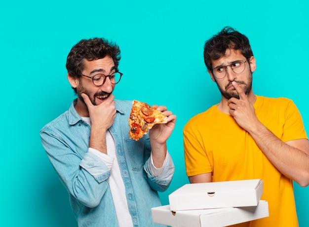 Twee spaanse vrienden die expressie denken en pizza's meenemen