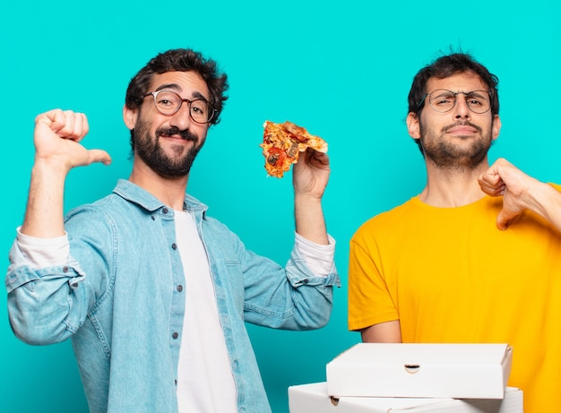 Twee spaanse vrienden met een gelukkige uitdrukking en met afhaalpizza's?