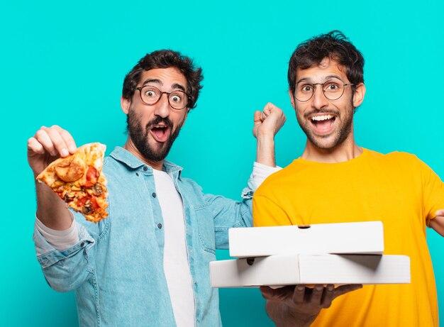 Twee spaanse vrienden verraste uitdrukking en hielden afhaalpizza's vast