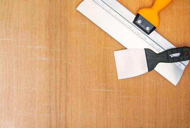 Twee spatels voor huisreparatie. brede en smalle tools op houten achtergrond.