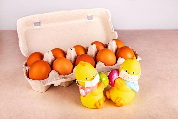 Twee speelgoedkippen in medische maskers in quarantaine met gekleurde eieren op de tafel bij de ecologische verpakking met oranje kippeneieren