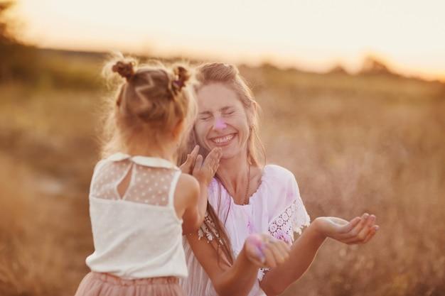 Twee spelen met de kleur in holi festival. moeder en dochter worden gespeeld op de aard van de kleuren.