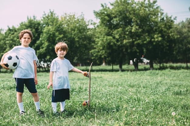 Twee sport jongens met een voetbal en een skateboard buitenshuis.