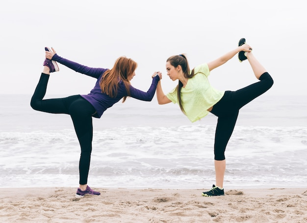 Twee sportenmeisjes die zich op het strand uitrekken