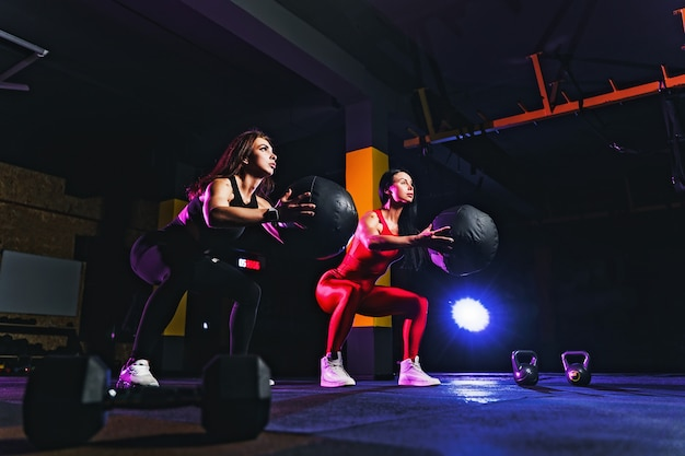 Twee sportenvrouwen die hurkende oefeningen met fitness bal doen. wijfje die en zich met geneeskundebal bij gymnastiek uitoefenen uitrekken