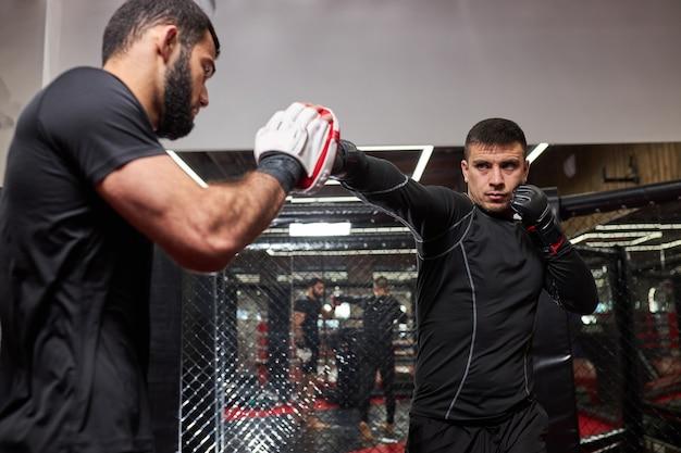 Twee sportieve mannen boksers die kickboksen oefenen in de ring in de healthclub of sportschool, oefenen met vechten, mma, in actie. sport, fintess, kickboks concept