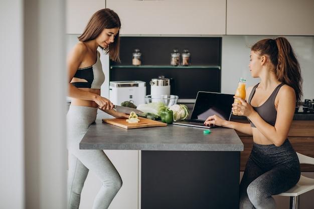 Twee sportieve meisjes die bij keuken voedsel bereiden