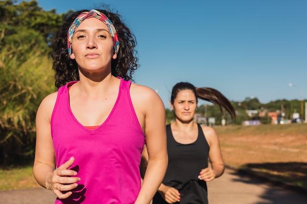 Twee sportvrouwen rennen buiten