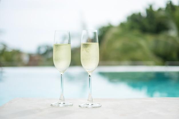 Twee sprankelende champagneglazen of prosecco bij zwembad