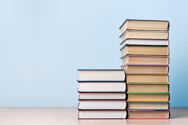 Twee stapels boeken van verschillende hoogte staan op een houten tafel tegen een lichtblauwe muur