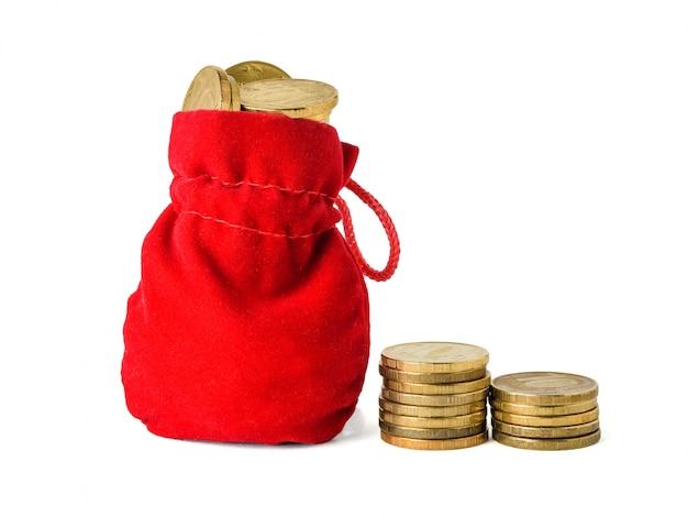 Twee stapels munten en een rode zak gevuld met munten geïsoleerd op wit. het concept van het sparen van contant geld.